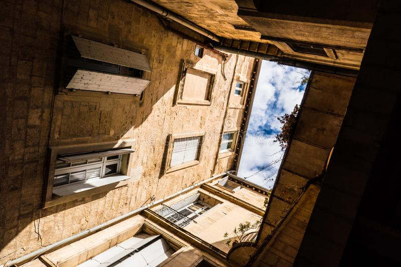 Courtyard and glimpse of sky. Glimpse of sky seen from a square courtyard of a building in a city in the south of France stock photography