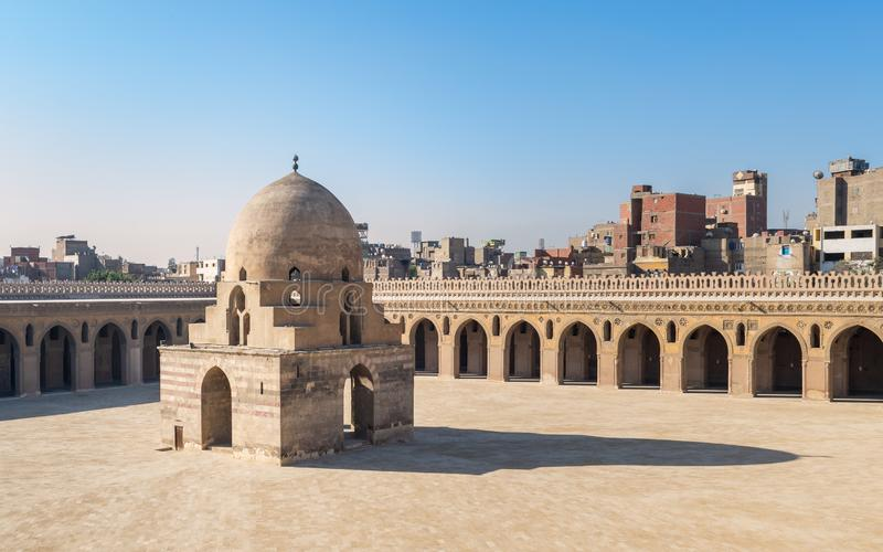 Courtyard of Ibn Tulun public historical mosque with ablution fountain and arched passages, Medieval Cairo, Egypt. Courtyard of Ibn Tulun public historical royalty free stock photography