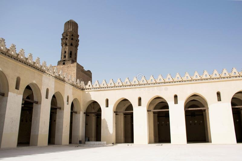 Courtyard of a mosque in the old city part of cairo egypt. White arched walls and minaret in the corner. royalty free stock photo