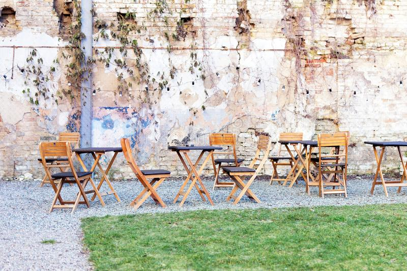 Courtyard outdoor cafe area with wooden tables and chair, green grass lawn and ruined shbby brick wall on the background. Open air royalty free stock images