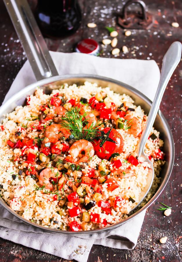 Couscous with fried prawns, mixed vegetables, pine nuts served in a cooking pan on a wooden table, selective focus. Traditional ea royalty free stock images