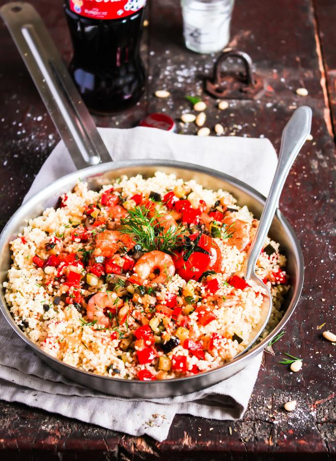 Couscous with fried prawns, mixed vegetables, pine nuts served in a cooking pan on a wooden table, selective focus. Traditional ea stock images