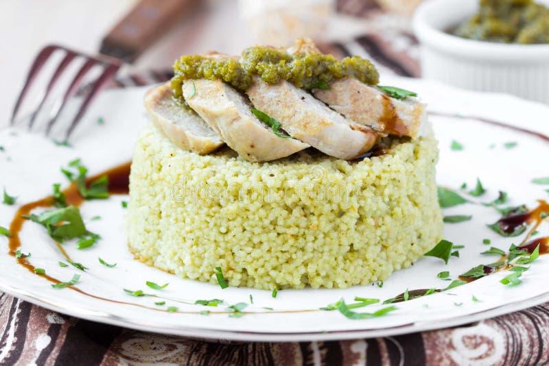 Couscous med pestosås, stekt skivat griskött, smaklig maträtt arkivfoto