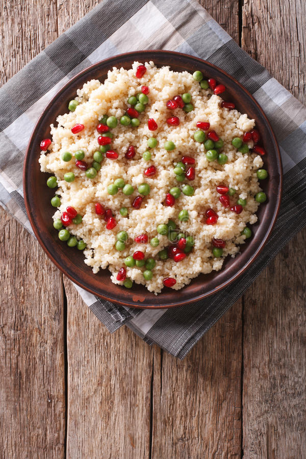 Couscous salad with green peas and pomegranate. vertical top vie royalty free stock images