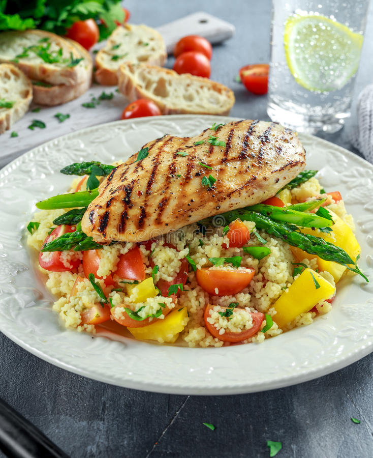 Couscous salad with grilled chicken and asparagus on white plate. healthy food stock images