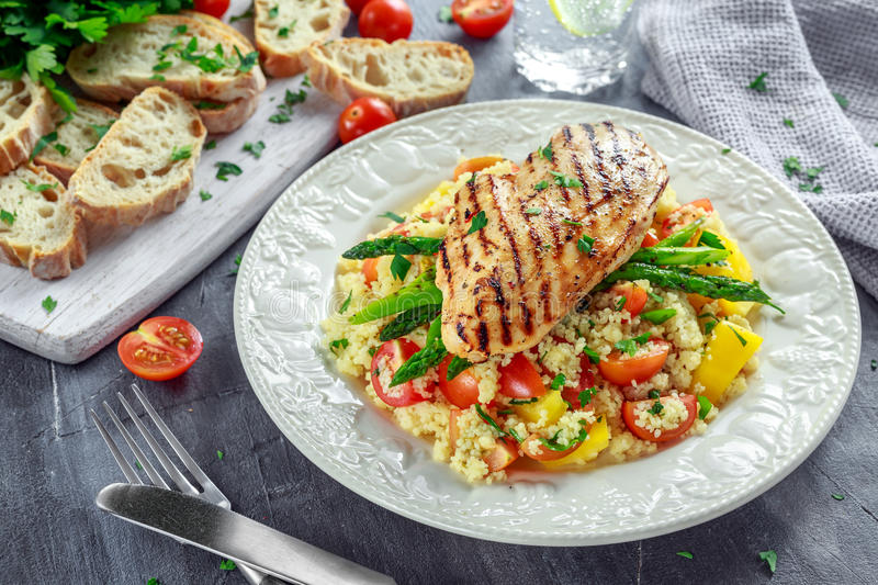 Couscous salad with grilled chicken and asparagus on white plate. healthy food stock photography