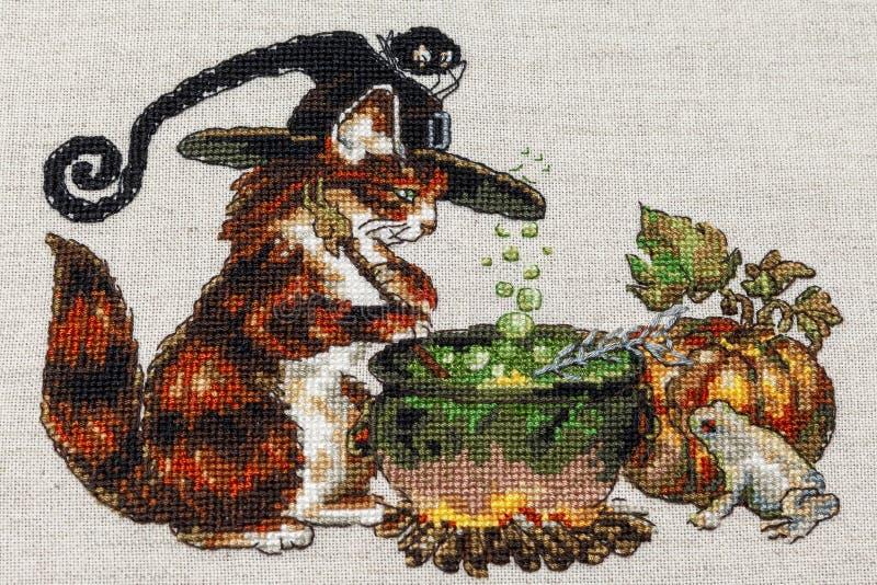 Cousez au point de croix la broderie avec le chat en chapeau, chaudron, crapaud, feu et potiron photographie stock