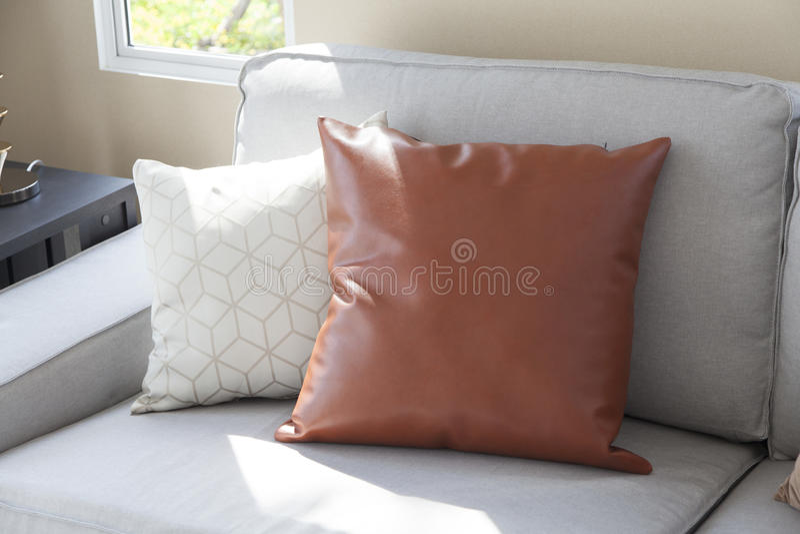 Coussin beige sur le sofa gris photographie stock