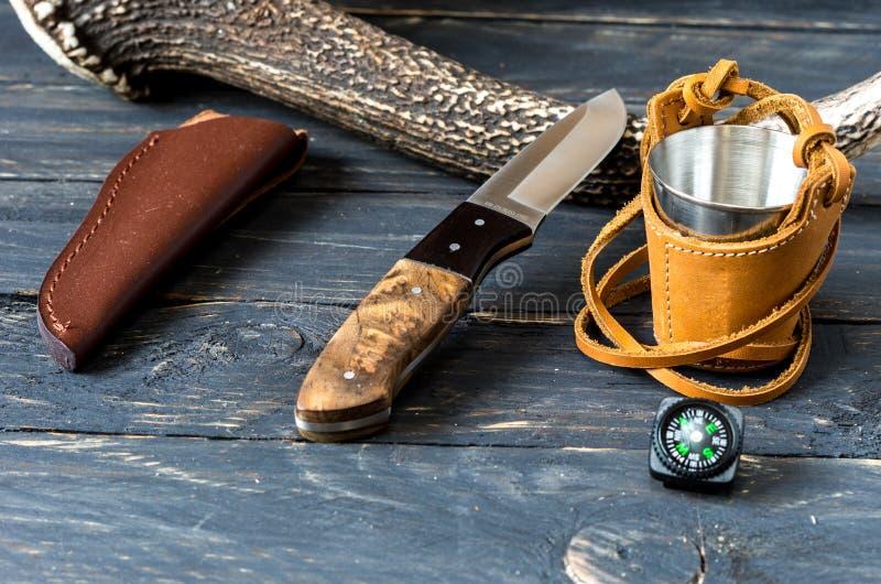 Couteau avec une gaine fixe de lame et de cuir près de klaxon de cerfs communs image libre de droits