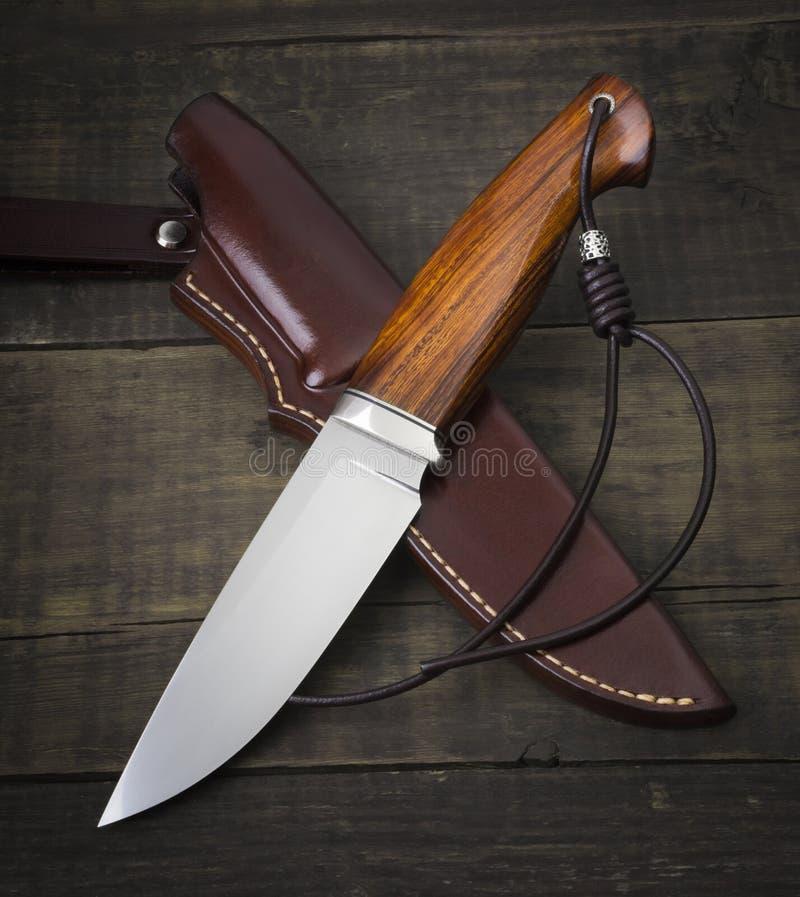 Couteau de chasse fait main sur un fond en bois brun Gaine en cuir faite main photo libre de droits