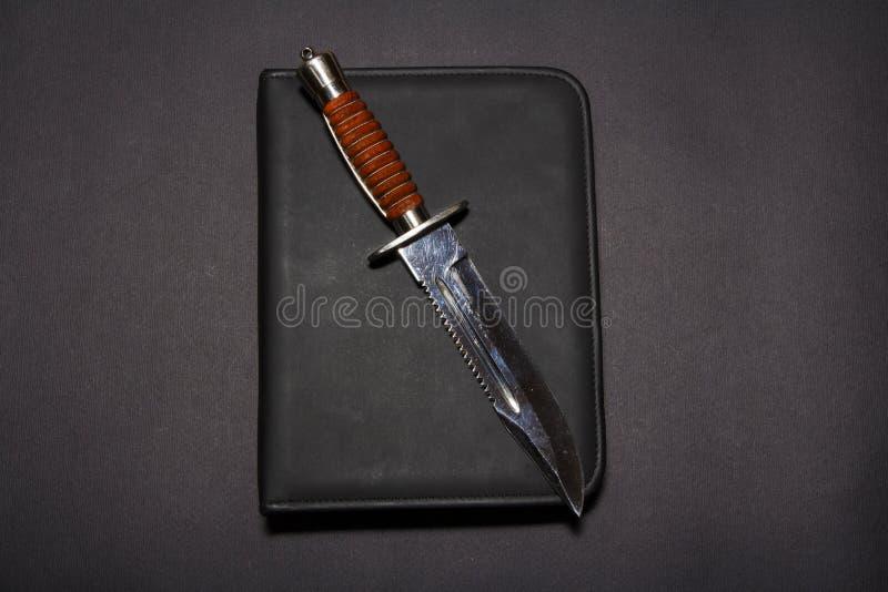Couteau de chasse sur un fond noir avec le dossier en cuir Couteau sur un fond noir Couteau images stock
