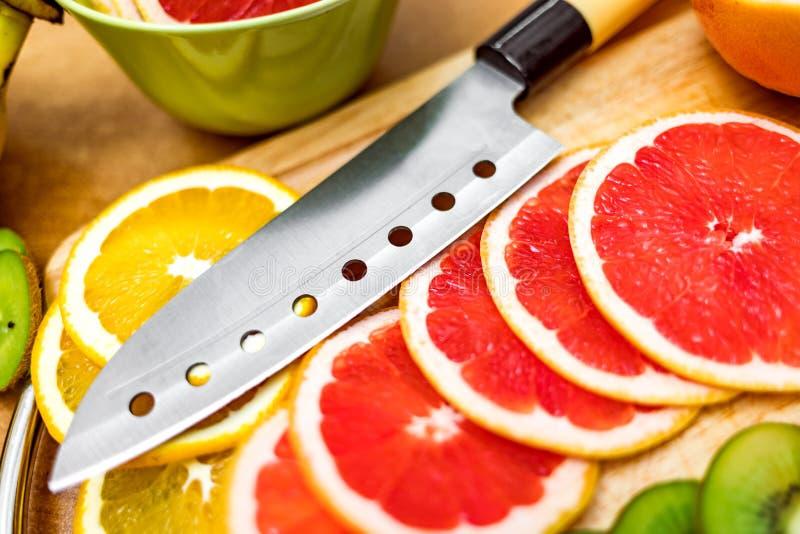 Couteau de cuisine pointu sur la planche à découper à côté du pamplemousse coupé en tranches a images stock
