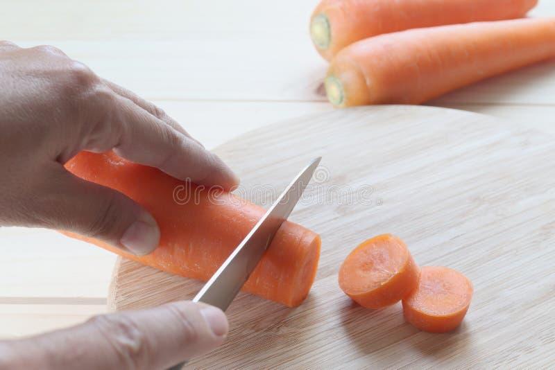 Couteau de prise de main coupant la carotte sur le conseil en bois photographie stock
