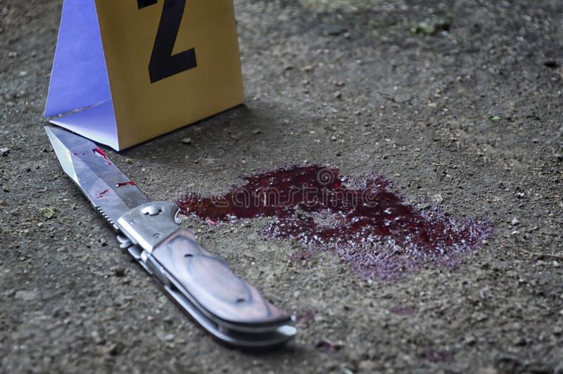 Couteau ensanglanté et marqueurs criminels sur la terre, preuves de homicide C image libre de droits