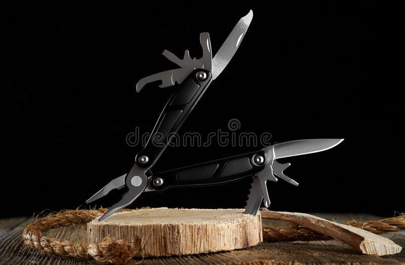 Couteau et corde de Multitool sur un fond foncé image stock