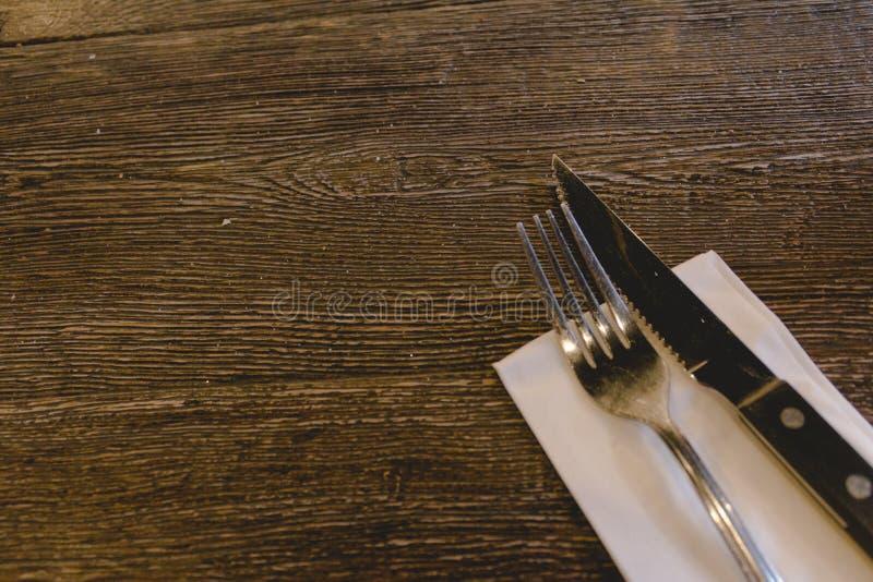 Couteau et fourchette sur une table en bois avec la serviette blanche image libre de droits