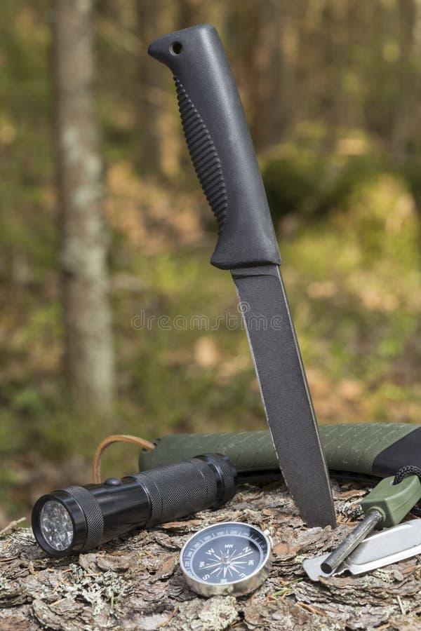 Couteau, lampe-torche, boussole, silex sur le tronçon dans le camping de forêt en nature image stock