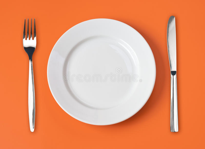 Couteau, plaque blanche et fourchette sur l'orange photographie stock