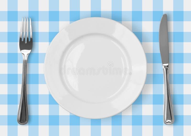 Couteau, plaque blanche et fourchette sur le bleu contrôlé images stock