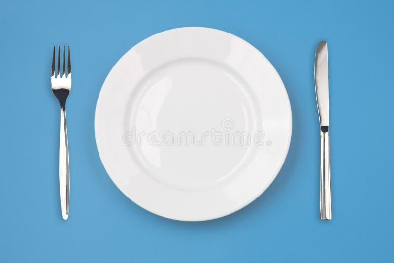 Couteau, plaque et fourchette sur le fond coloré photographie stock libre de droits