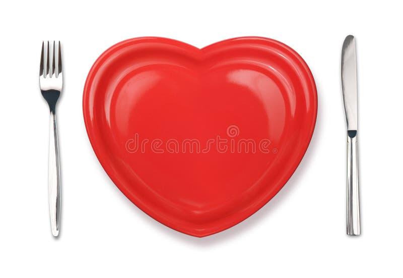Couteau, plaque rouge dans la forme de coeur et fourchette photo libre de droits