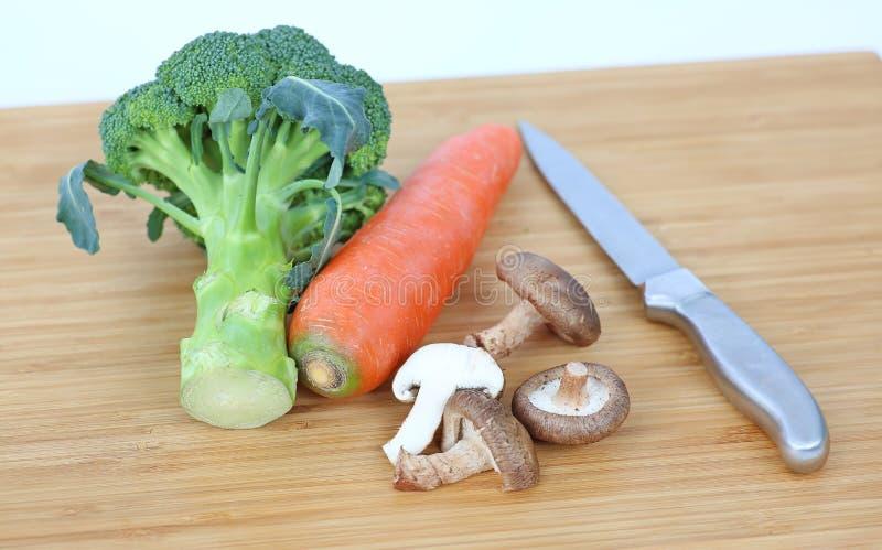 Couteau pointu avec le champignon de shiitaké végétal, piment, carotte, ail sur le bloc en bois photo stock