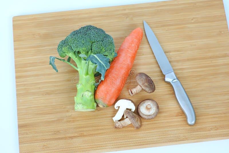 Couteau pointu avec le champignon de shiitaké végétal, piment, carotte, ail sur le bloc en bois photo libre de droits