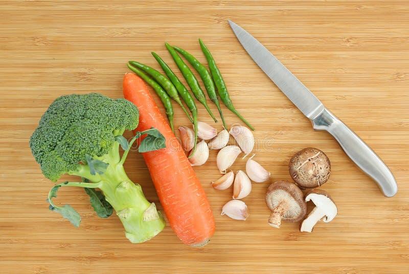 Couteau pointu avec le champignon de shiitaké végétal, piment, carotte, brocoli, ail sur le bloc en bois photographie stock