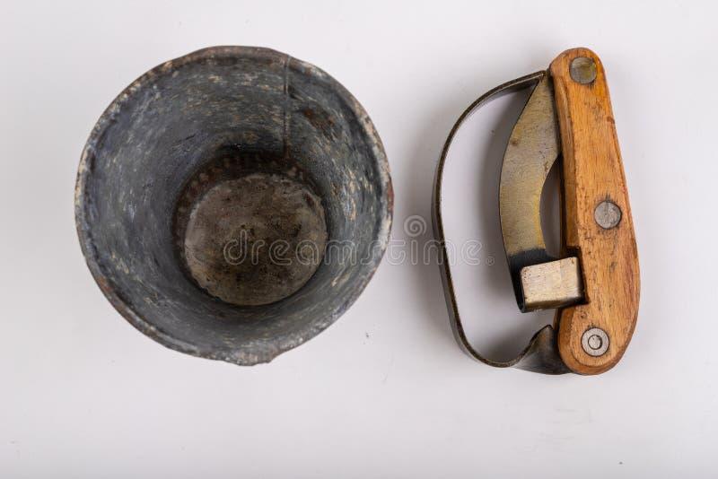 Couteau pour des arbres d'écorcement et un conteneur en métal pour la résine sur une table blanche Accessoires pour obtenir la ré photographie stock