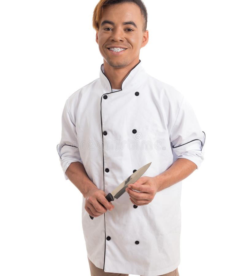 Couteau professionnel de coffre-fort de cuisine Le jeune homme de couleur est dans le roucoulement blanc photos stock