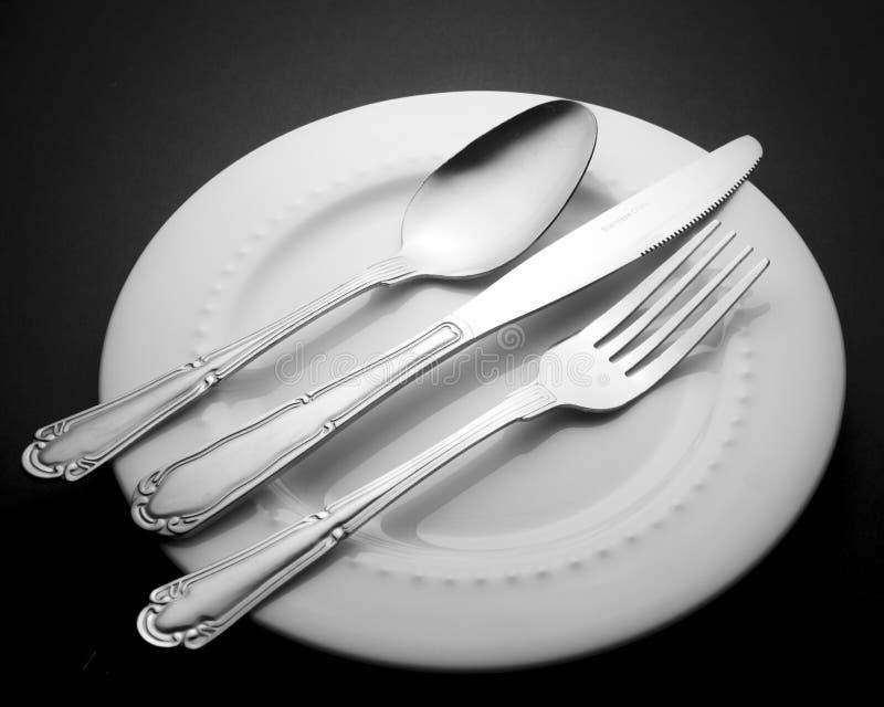 Couteau réglé et cuillère de fourchette de couverts d'isolement sur les ustensiles blancs de cuisine de plat photo libre de droits