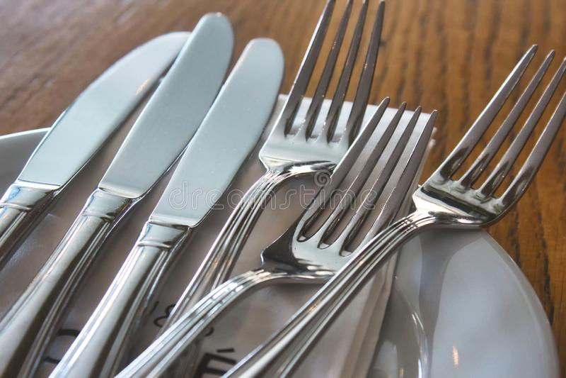 Couteaux de couverts et fourchettes et un plat en céramique sur une table dans un restaurant photographie stock libre de droits