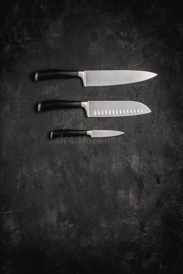 Couteaux de cuisine modernes réglés sur le fond en pierre Concept des couteaux du chef photo stock