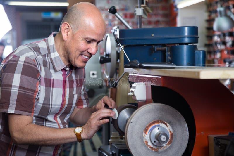 Couteaux resharpering d'ouvrier supérieur sur la machine de système de roue de spirale de couplage photos stock