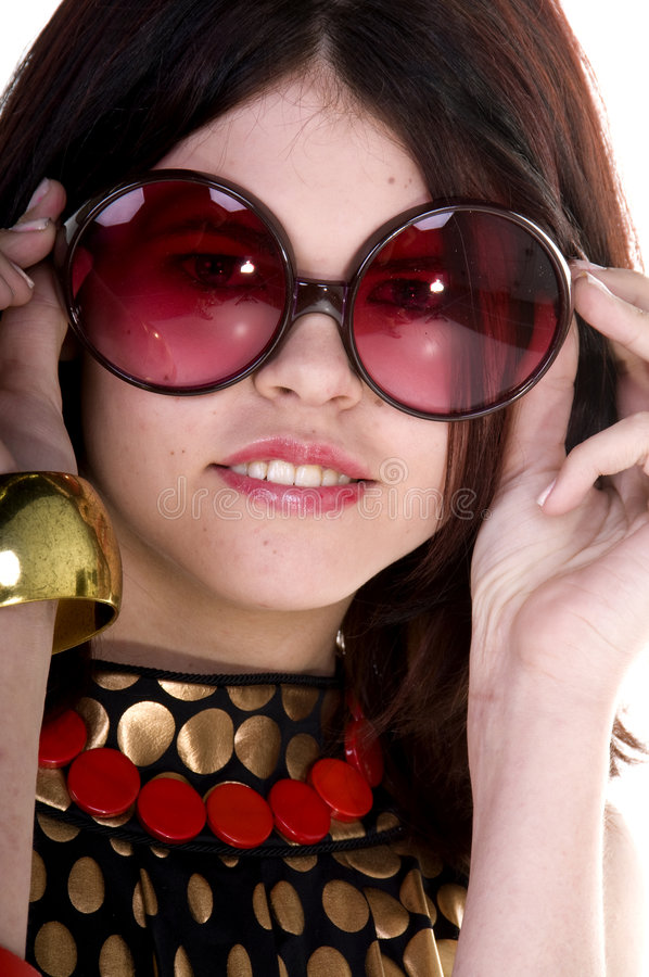 Couture Fashion Model. Close up of a beautiful and hip young woman in a black and gold Couture dress and big retro sunglasses stock image