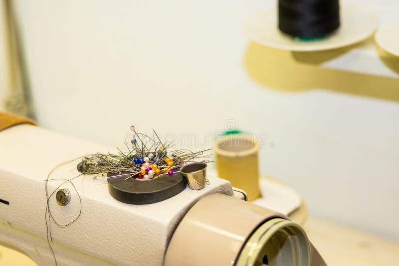 Couture, piquant, cousant et travaillant le concept - goupilles colorées sur l'aimant sur la machine à coudre, outils plan rappro photo stock