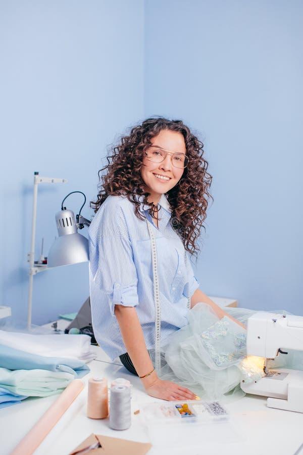 Couturière de sourire s'asseyant dans le bureau ayant le textile sur des mains image stock