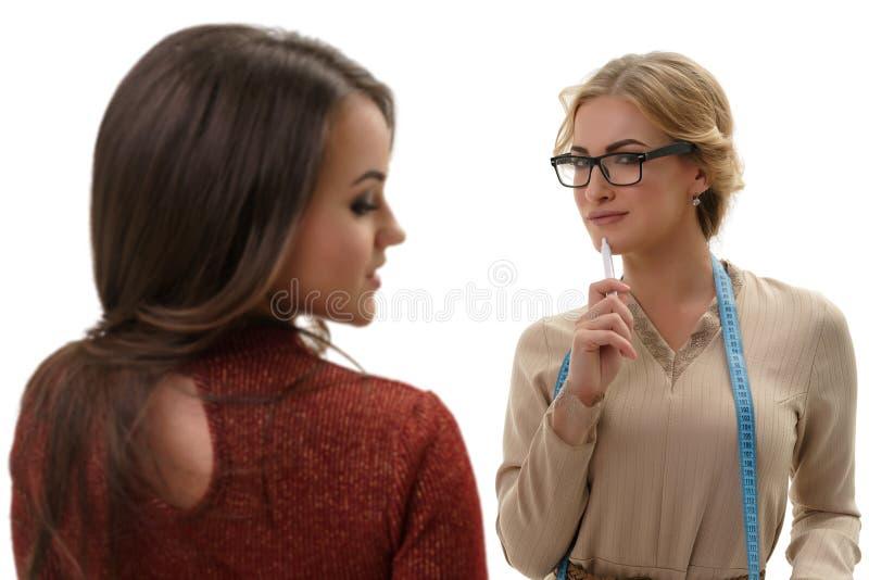 Couturière et client féminin d'isolement sur le blanc image libre de droits