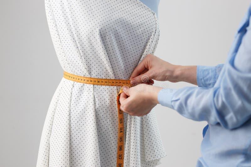 Couturière féminine travaillant sur le nouveau modèle travaillant la robe sur le mannequin dans le studio photo libre de droits
