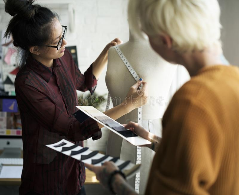 Couturier à l'aide d'une bande de mesure sur un mannequin photographie stock libre de droits