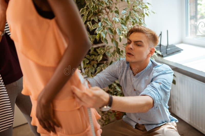 Couturier adaptant la robe sur le modèle images libres de droits