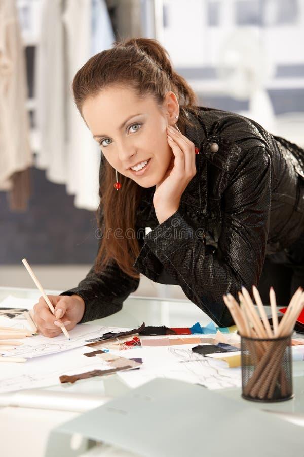 Couturier assez jeune travaillant dans le studio photo stock