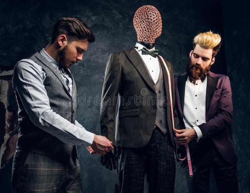 Couturier avec un client vérifiant le costume des hommes faits sur commande dans un studio foncé de tailleur photos stock
