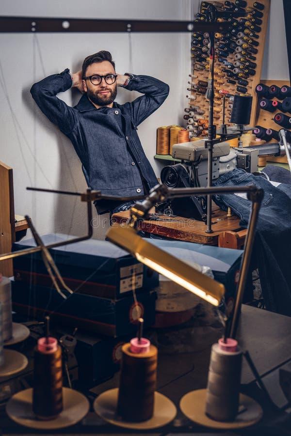 Couturier barbu beau faisant une pause de travail et pensant à de nouvelles conceptions dans un atelier de couture images stock