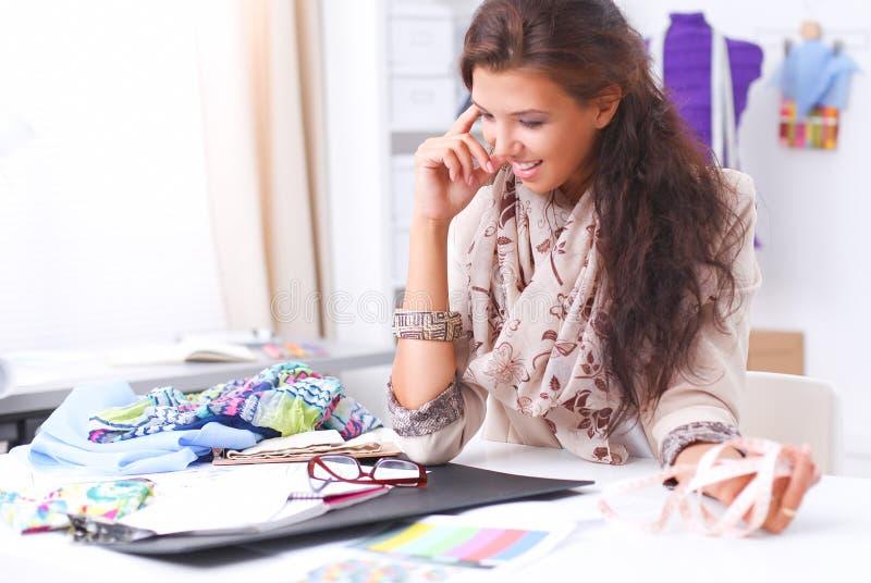 Download Couturier Féminin De Sourire S'asseyant Au Bureau Photo stock - Image du réussite, attrayant: 87701496