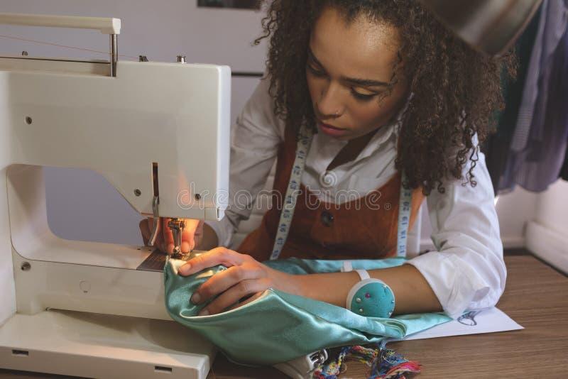 Couturier féminin travaillant avec la machine à coudre image libre de droits