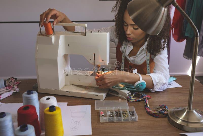 Couturier féminin travaillant avec la machine à coudre photos stock