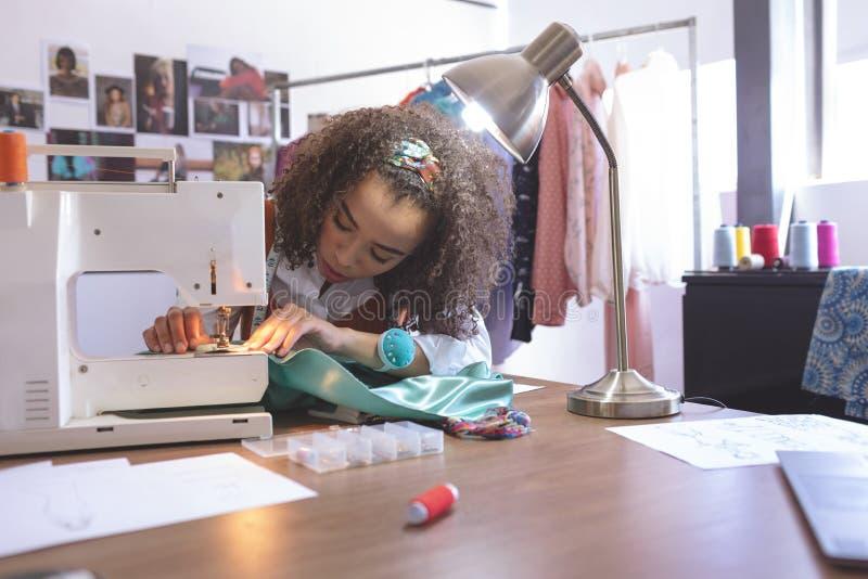Couturier féminin travaillant avec la machine à coudre photo libre de droits