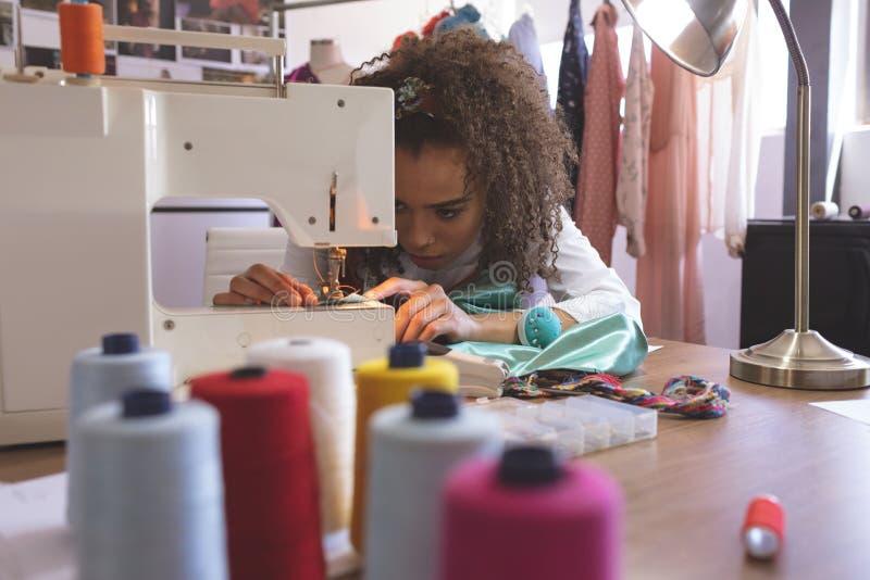 Couturier féminin travaillant avec la machine à coudre images libres de droits