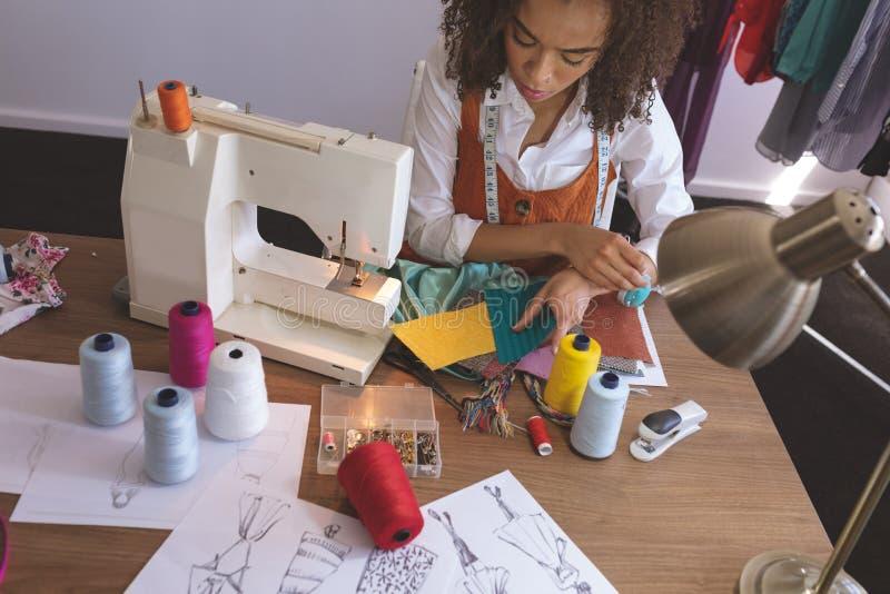 Couturier féminin travaillant dans le studio de conception photo stock